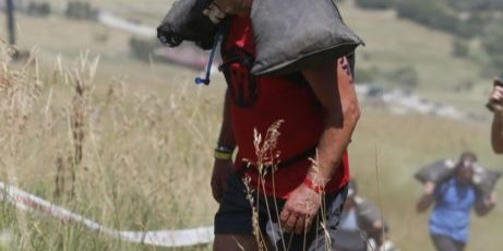 Red Shoes Living founder Lonnie Mayne carrying sandbag up hill in Spartan Race